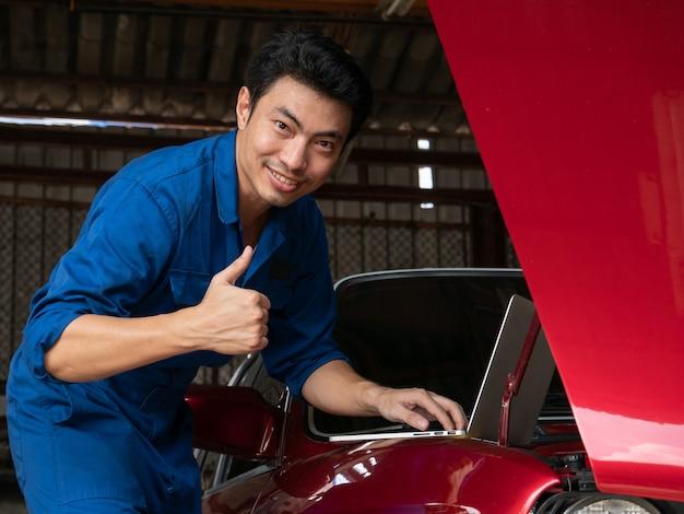 Knappe aziatische mechanische gebruikende laptop computer om een motor van een auto te controleren en duimen te tonen omhoog bij de reparatiegarage.