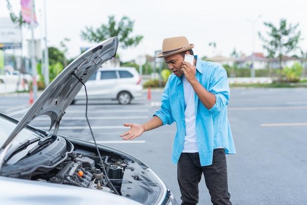 Knappe aziatische mens die de autodienst roepen van de telefoongespreknoodsituatie.