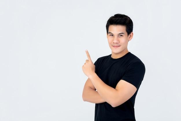 Knappe aziatische mens die en hand omhoog naar lege ruimte glimlacht richt