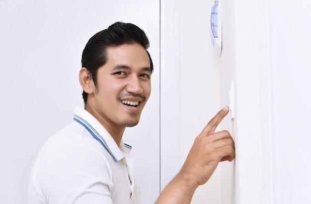Knappe aziatische mens die het licht met muurschakelaar uitzet