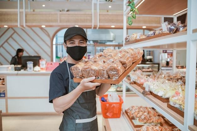 Knappe aziatische werknemer bij de bakkerijwinkel die masker draagt tijdens nieuw normaal open voor zaken