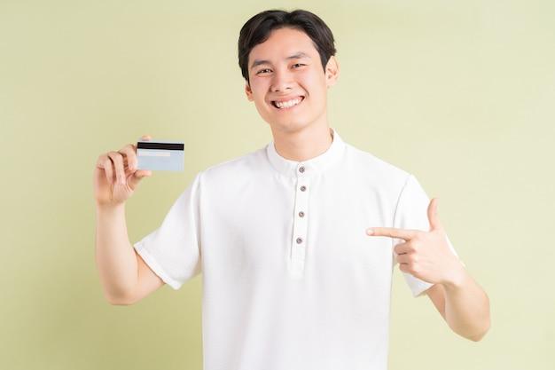 Knappe aziatische zakenman die en zijn vinger op creditcard glimlacht richt