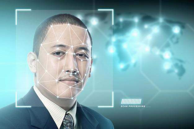 Knappe aziatische zakenman die gezichtsherkenning gebruikt