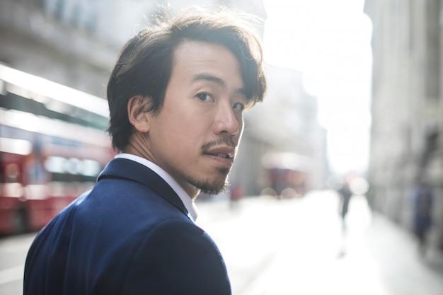 Knappe aziatische zakenman die in de straat loopt