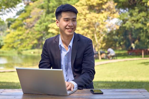Knappe aziatische zakenman die laptop met behulp van