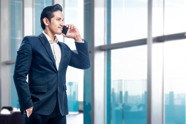 Knappe aziatische zakenman die zich terwijl het spreken op cellphone bevindt