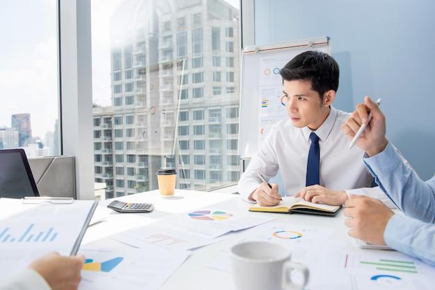 Knappe aziatische zakenman in verkoopvergadering