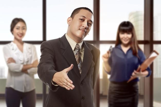 Knappe aziatische zakenman met open hand klaar voor handschok