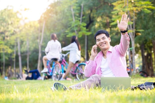 Knappe aziatische zakenman ontspant en gebruikt smartphone-stem die met zijn vriend op groen gras in een central park wordt gebeld