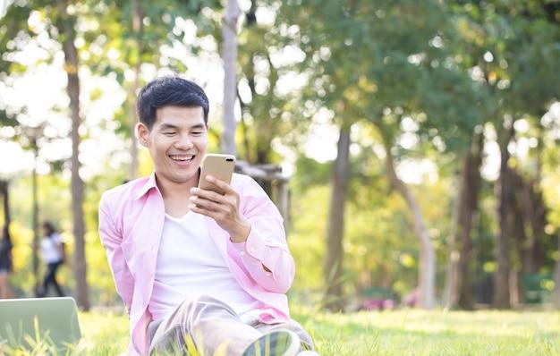 Knappe aziatische zakenman ontspant en gebruikt smartphone-videogesprek met zijn vriend op groen gras in een central park