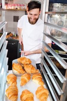 Knappe bakker in witte uniforme houden in zijn handen een dienblad vol met vers gebakken croissants tegen het oppervlak van een bakkerij