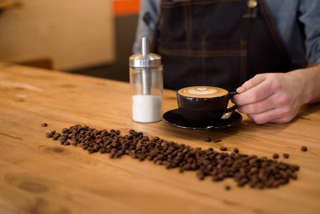Knappe barista die een kop van koffie houdt bij de koffie