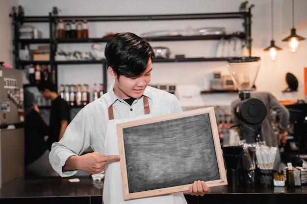 Knappe barista die en een bord op tribune voor pub houdt richt