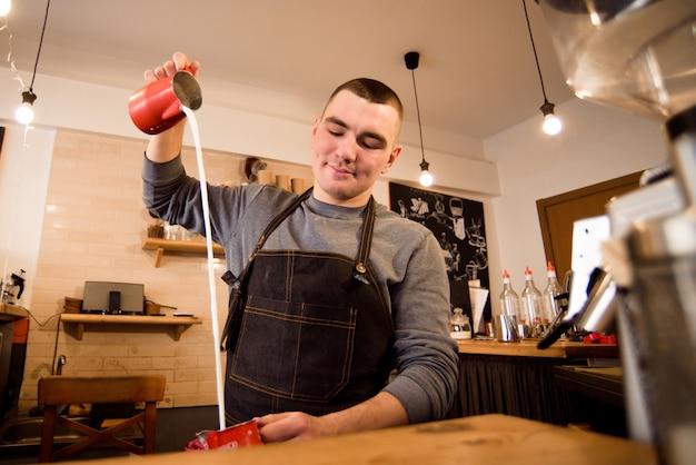 Knappe barista die kop van koffie voor klant in koffiewinkel voorbereiden.