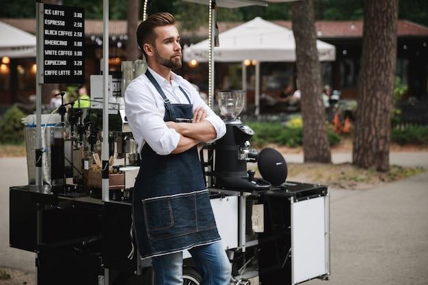 Knappe barista-man tijdens het werk in zijn verplaatsbare straatcoffeeshop