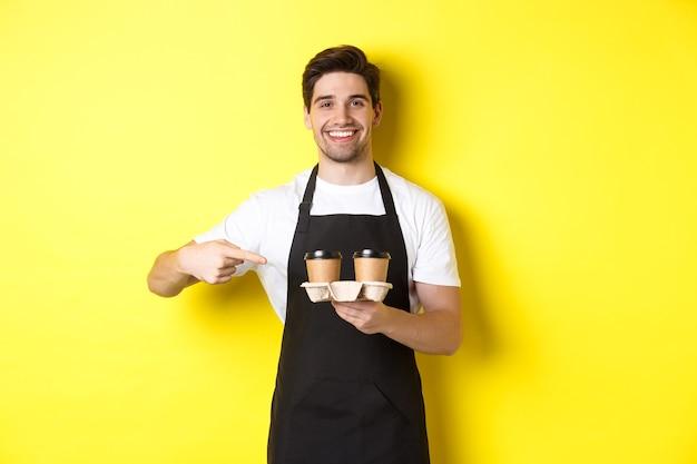 Knappe barista met twee kopjes afhaalkoffie, wijzende vinger naar drankjes en glimlachend, staande in zwarte schort tegen gele achtergrond.