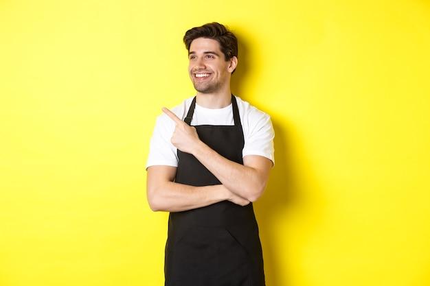 Knappe barista wijzend en kijkend naar links naar promo, gekleed in een zwarte schort, staande tegen een gele achtergrond.