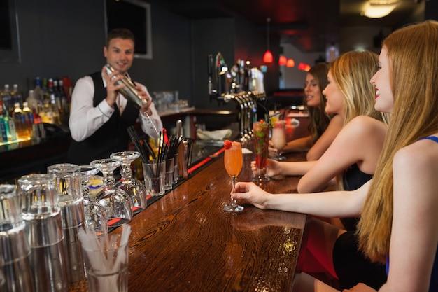 Knappe barman die cocktails maakt voor aantrekkelijke vrouwen