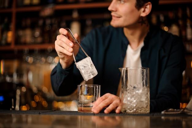 Knappe barman die een groot ijsblokje zet in een glas