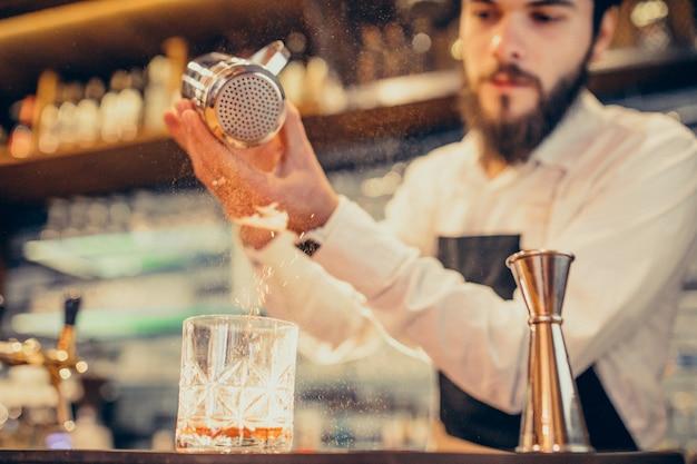Knappe barman drinken en cocktails aan een balie maken