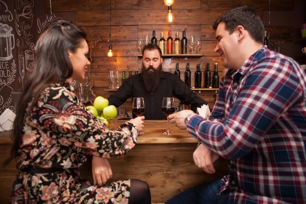 Knappe barman in gesprek met klanten aan toog in een pub. hippe kroeg.