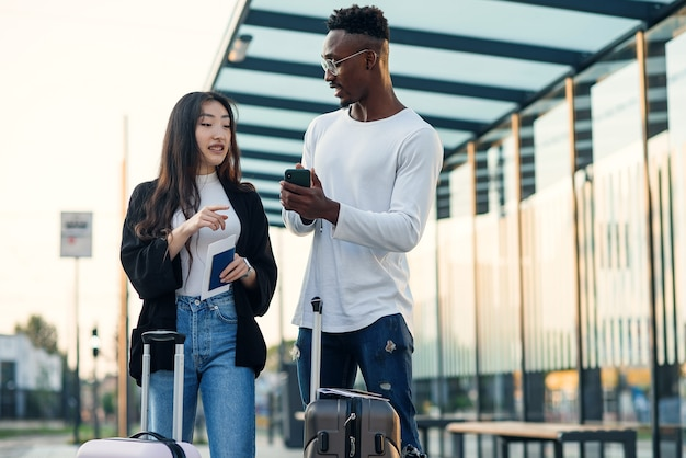 Knappe bebaarde afro-amerikaanse jongen en aziatische mooi meisje verzamelen op zakenreis met koffers te wachten bij stop.