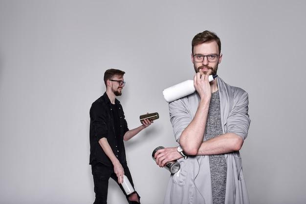Knappe bebaarde barmannen tweeling jongleren met shaker en flessen
