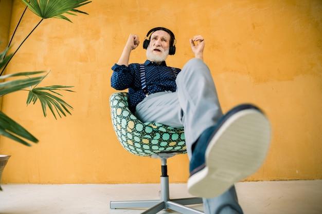 Knappe bebaarde bejaarde man, gekleed in stijlvolle hipster kleding, ontspannen in de stoel terwijl hij luistert naar zijn favoriete muziek in de koptelefoon. studio die op gele achtergrond is ontsproten
