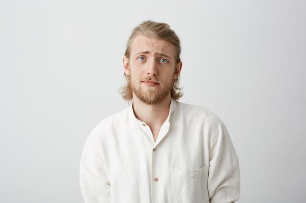 Knappe bebaarde blanke man met blond haar die wenkbrauwen optilt, ziet er heel schattig en somber uit alsof hij om gunst vraagt of advies vraagt
