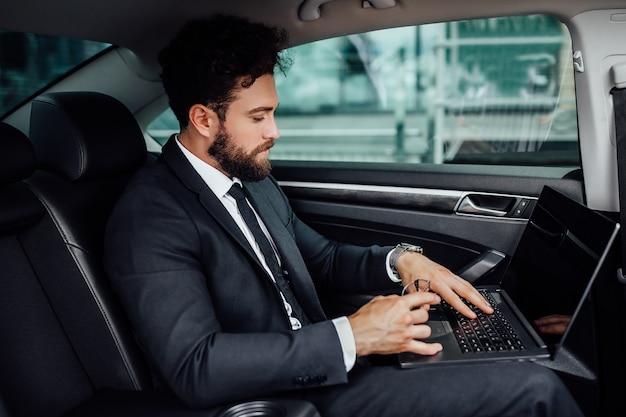 Knappe, bebaarde, glimlachende topmanager in zwart pak die op zijn laptop op de achterbank van de auto werkt