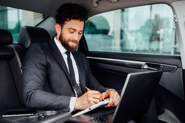 Knappe, bebaarde, glimlachende zakenman die op de achterbank van de auto werkt en notities maakt in het notitieboekje vanaf zijn laptop