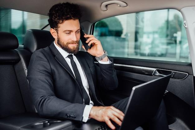 Knappe, bebaarde, glimlachende zakenman die op zijn laptop werkt en een mobiele telefoon spreekt op de achterbank van de auto