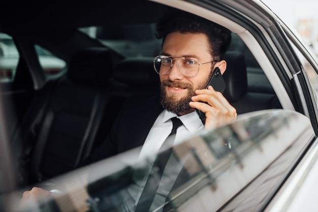 Knappe, bebaarde, glimlachende zakenman in zwart pak die belt op de achterbank van de auto
