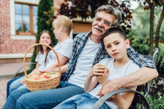 Knappe, bebaarde grootvader ontspannen met zoon op tuin, familie tijd..