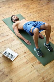 Knappe bebaarde heer in korte broek doet oefeningen met weerstandsband terwijl hij op fitnessmat in de buurt van laptop ligt