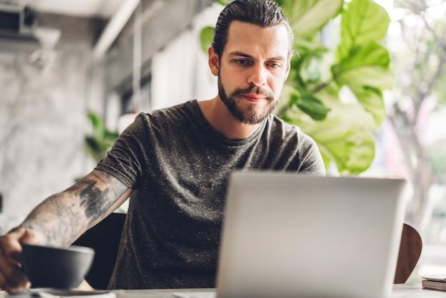 Knappe bebaarde hipster man gebruik en kijken naar laptopcomputer met koffie aan tafel in café.communicatie en technologie concept