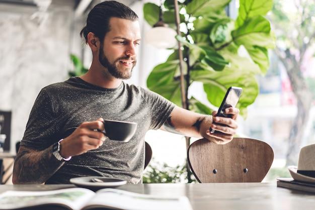Knappe bebaarde hipster man gebruik smartphone met koffie aan tafel in café. communicatie en technologie concept
