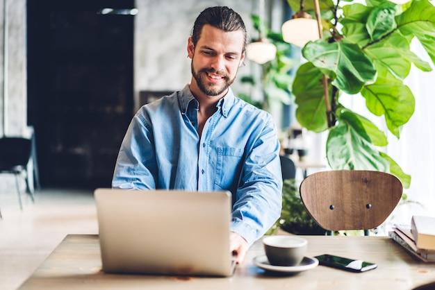 Knappe bebaarde hipster man gebruiken en kijken naar laptopcomputer met koffie aan tafel in café.communicatie en technologie concept