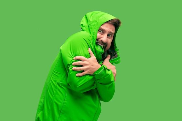 Knappe bebaarde ijskoude jonge man geïsoleerd op levendige trendy groene kleur in de studio. concept van het begin van de herfst en kou