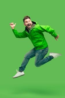 Knappe bebaarde jonge man loopt geïsoleerd op groen