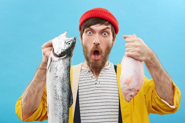 Knappe bebaarde jonge visser die twee vissen vasthoudt die hij net heeft gevangen