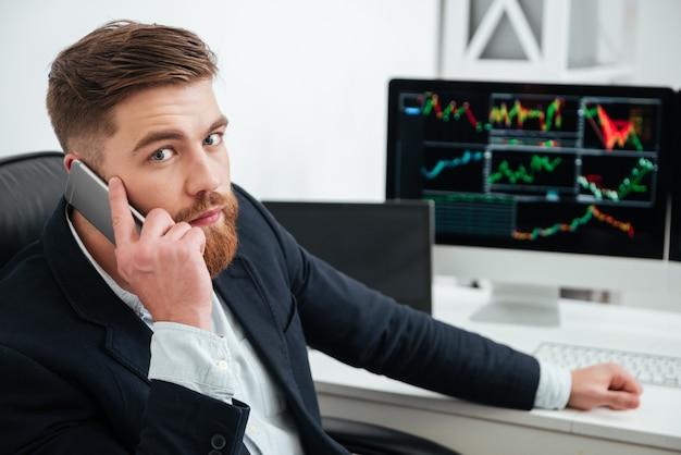 Knappe bebaarde jonge zakenman praten op mobiele telefoon in office