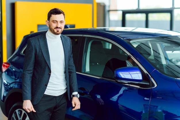 Knappe bebaarde koper in vrijetijdskleding bij dealer, kerel kijkt op camera terwijl hij in de buurt van auto met gekruiste armen staat