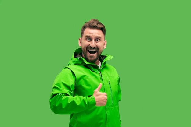Knappe bebaarde lachende gelukkig jonge man kijken camera geïsoleerd op levendige trendy groene studio.