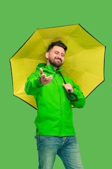 Knappe bebaarde lachende gelukkig jonge man paraplu te houden en camera te kijken