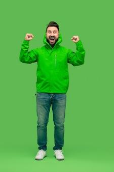 Knappe bebaarde lachende gelukkige jonge man kijkt naar voorzijde geïsoleerd op levendige trendy groene studio