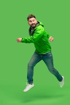 Knappe bebaarde lachende gelukkige jonge man loopt geïsoleerd op levendige trendy groene studio. concept van de herfst en koude tijd. menselijke emoties concepten