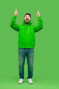 Knappe bebaarde lachende gelukkige jonge man op zoek en omhoog geïsoleerd op levendige trendy groene studio. concept van de herfst en koude tijd