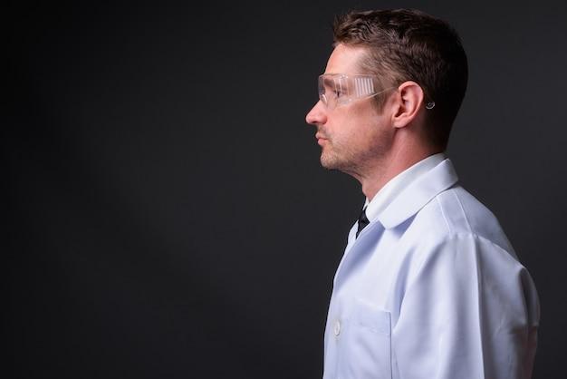 Knappe bebaarde man arts als wetenschapper met beschermende bril tegen grijze muur