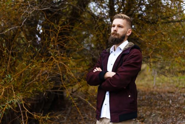 Knappe bebaarde man buitenshuis portret staat tegen de achtergrond van de herfst natuur in het park in...